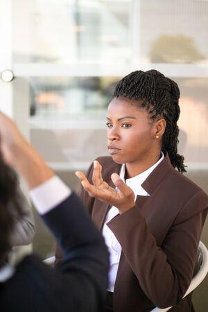 Empresaria confiada seria que escucha a los socios durante la reunión. Equipo de negocios sentado a la mesa y hablando. Concepto de negociación Foto de archivo
