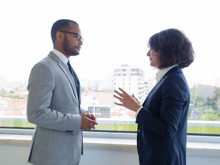 Senior employee instructing newcomer. Business man and woman standing indoors near window and talking. Office communication concept