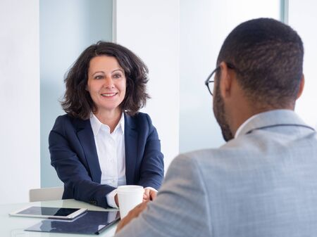 Smiling female job candidate talking to employer during interview. Business man and woman sitting at meeting table and talking. Career concept Imagens