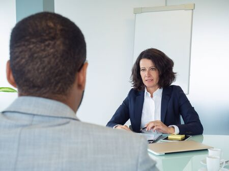 Corporate trainer explaining work details to new employee. Business man and woman sitting at meeting table opposite of each other. Instructing concept Stock Photo