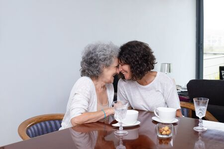 Happy mother with adult daughter laughing together. Cheerful senior mother and middle aged daughter sitting together at table with cups and glasses. Togetherness concept