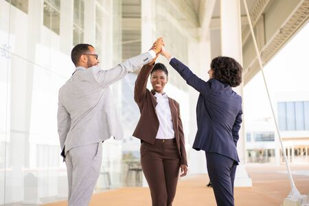 Happy joyful business colleagues celebrating success. Multiethnic team of man and women giving high five to each other. Team success concept