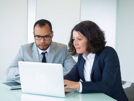 Excited business team working on project together. Business man and woman sitting at office table, using laptop and staring at screen. Business team concept