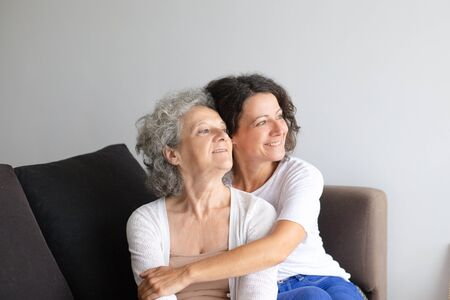 Happy daughter hugging senior mother. Cheerful senior mother and middle aged daughter sitting together on couch and looking aside at home. Togetherness concept