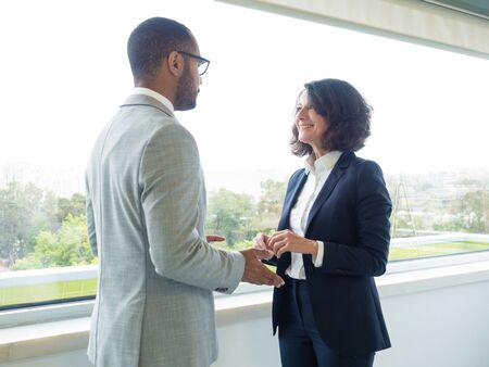 Coworkers discussing project in office corridor. Business man and woman standing indoors near window and talking. Business conversation concept Stock Photo