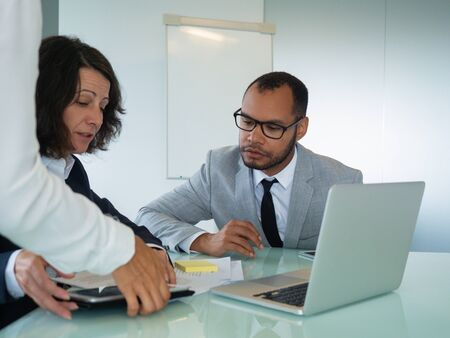Female mentor training young male intern. Business man and woman sitting at meeting table, studying papers and software on laptop. mentorship concept