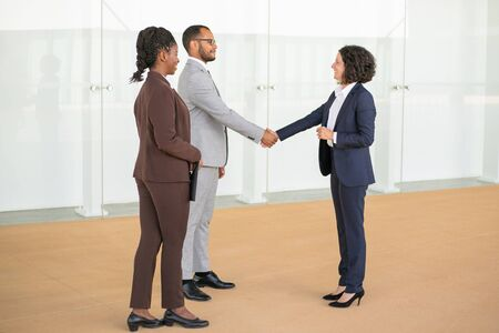 Friendly business colleagues greeting each other in office hallway. Multiethnic business man and women standing in hallway and shaking hands. Business communication concept