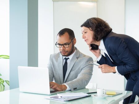 Professional team using gadgets for work on project. Business man and woman talking on cellphone, using laptop and looking at screen. Communication for business concept Stock Photo