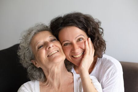 Happy mother and daughter spending time together at home. Cheerful senior mother and middle aged daughter embracing and smiling at camera. Family concept