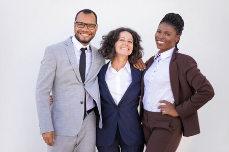 Successful united business team posing for camera. Line of joyful multiethnic man and women hugging each other and smiling. Successful team portrait concept