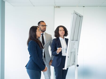 Business group of three studying drawing on whiteboard. Business woman standing at white board with marker, her two colleagues listening to her. Boardroom concept