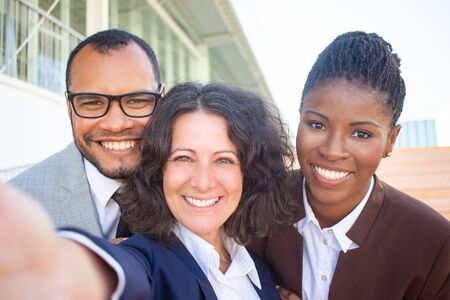 Happy female business leader taking group selfie with her team. Self portrait of successful business man and women. Group selfie team concept