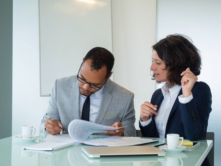 Businesswoman waiting her partner signing contract. Business man and woman sitting at meeting table, reading and signing papers. Signing contract concept