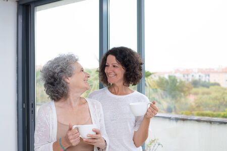 Happy mother and daughter holding cups. Cheerful senior mother and daughter daughter holding white mugs and smiling each other. Togetherness concept