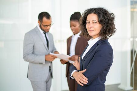 Happy confident female business leader posing while her team working. Middle aged businesswoman standing with arms folded and smiling. Successful business woman concept