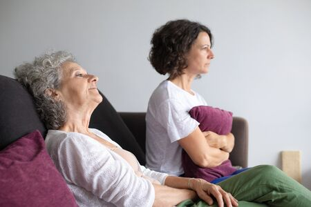 Unhappy mother and daughter at home. Side view of upset senior mother and middle aged daughter sitting together on couch. Conflict concept Stockfoto
