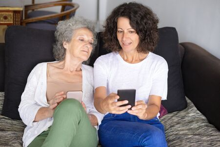 Smiling mother and daughter using smartphones. Cheerful senior and middle aged women sitting together on couch and using mobile phones. Technology concept