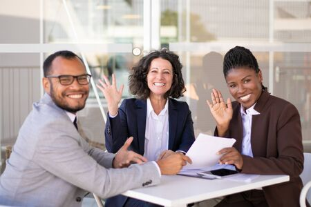 Happy successful business team posing at table and waving hello. Cheerful multiethnic man and women sitting in outdoor cafe and smiling at camera. Team success concept