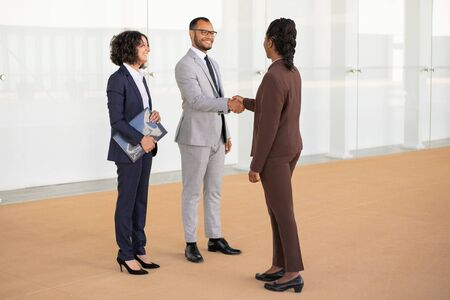 Happy business partners greeting each other in office hallway. Multiethnic business man and women standing and shaking hands. Partnership concept