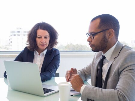 Female professional teaching male intern to work with corporate software. Business man and woman sitting at open laptop, looking at screen and talking. Job training concept Stockfoto