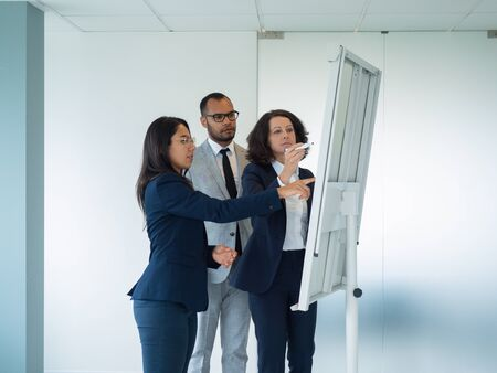 Young intern asking trainer about graphs on whiteboard. Business woman drawing on board, her two colleagues looking at her and pointing at drawing. Internship concept
