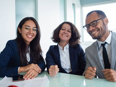 Happy business team posing for camera at meeting table. Cheerful man and women sitting in conference room and smiling. Successful team portrait concept