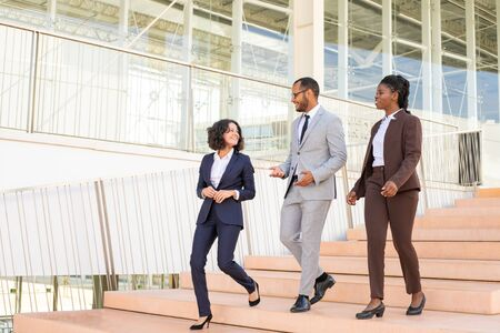 Cheerful business colleagues walking in office building. Three business man and women going down stairs, talking, laughing. Walking team concept