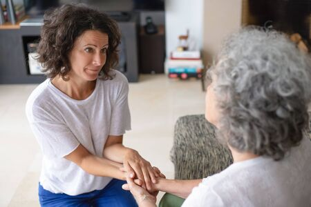 Senior mother and adult daughter holding hands. Smiling middle aged woman holding hands on elderly mother at home. Family concept Stockfoto