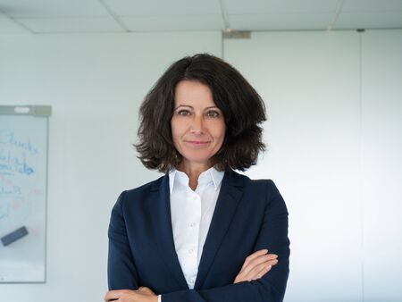 Successful female business trainer posing in boardroom. Businesswoman standing in office with arms folded and smiling at camera. Successful business woman concept Stockfoto
