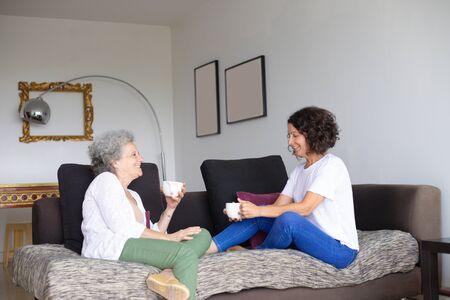 Senior mother with adult daughter drinking tea at home. Side view of cheerful middle aged woman with senior mother sitting on couch and holding cups. Spending time together concept Stockfoto