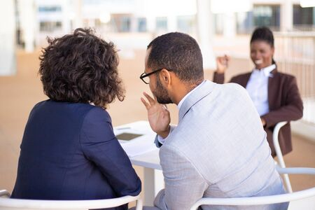 Male and female business colleagues whispering gossips about African American colleague. She laughing at them in background. Office conflict concept