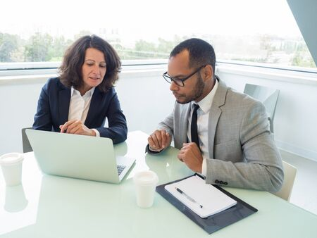 Female manager teaching male newcomer how to use corporate software. Business man and woman sitting at meeting table with open laptop and looking at screen. Internship concept Stockfoto