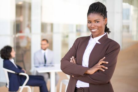 Happy successful business leader posing while her team in background. Young African American business woman standing with arms folded and smiling. Teamwork concept
