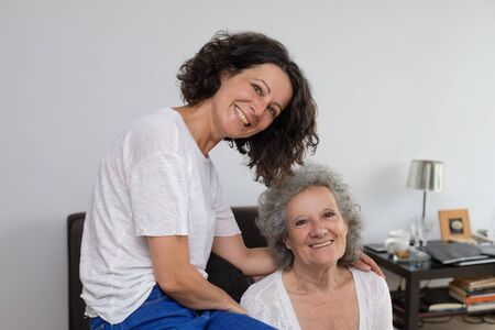 Cheerful mother and daughter smiling at camera. Happy senior mother and middle aged daughter sitting together and looking at camera at home. Togetherness concept