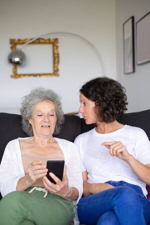 Senior and middle aged women using smartphone. Senior mother with adult daughter sitting together on couch and using mobile phone. Technology concept Stockfoto