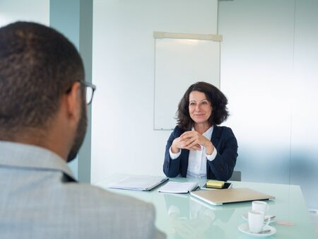 Female employer interviewing male applicant. Business man and happy woman sitting at meeting table opposite of each other. Interview concept Stockfoto