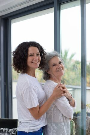 Happy mother and daughter standing near window. Cheerful senior mother and adult daughter standing together near window and smiling at camera. Togetherness concept Stockfoto