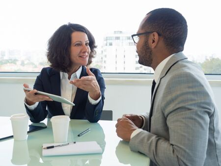 Senior employee telling newcomer about ongoing project. Confident business woman holding tablet and talking to male colleague at meeting table. New employee concept
