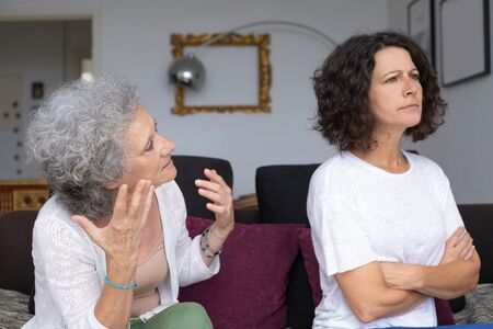 Senior mother and adult daughter quarrelling. Side view of middle aged daughter and old mother having conflict at home. Relationship problem concept Stockfoto