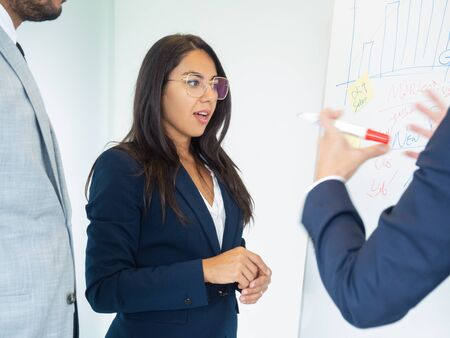 Young employee shocked with report. Young business woman standing at white board, and looking at drawn charts with open mouth and wide eyes. Shocking report concept