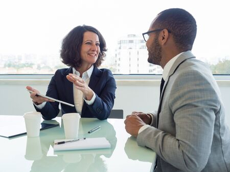 Joyful corporate trainer telling newcomer about work in company. Happy business woman holding tablet and talking to male colleague at meeting table. Newcomer concept Stockfoto