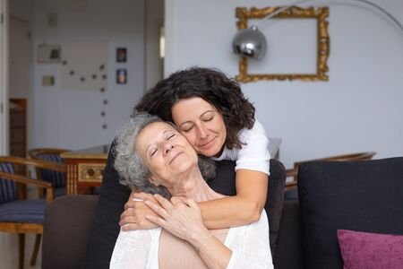 Mother and daughter with closed eyes hugging. Happy senior mother and middle aged daughter hugging together at home. Happiness concept Stockfoto