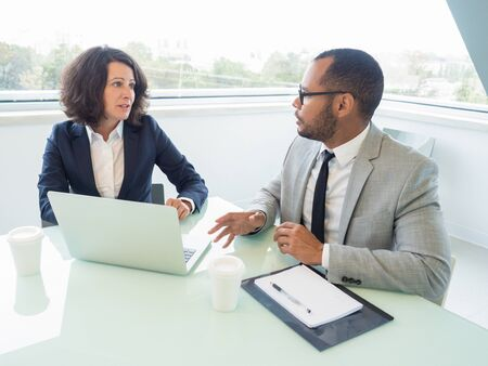 Business partners watching presentation and discussing project. Business man and woman sitting at meeting table with open laptop and talking. Partnership concept Stockfoto