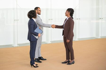 Happy business colleagues welcoming each other in office corridor. Multiethnic business man and women standing in hallway and shaking hands. Handshake concept