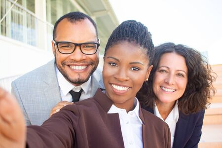 Happy black businesswoman taking group selfie with team. Self portrait of successful multiethnic business man and women. Collective selfie concept