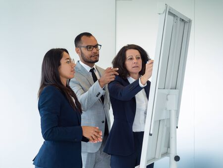 Trainer explaining work details to interns. Business woman drawing on board, her two colleagues looking and pointing at drawings. Teaching concept