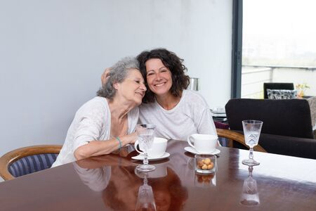 Happy mother and daughter hugging at home. Cheerful senior mother and middle aged daughter sitting together at table with cups and glasses. Family concept