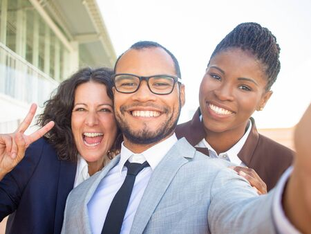 Joyful multiethnic business people taking group selfie. Self portrait of happy business man and women showing peace gesture. Multiethnic team concept