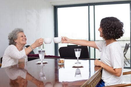 Happy mother and daughter clinking cups. Side view of cheerful senior mother and adult daughter sitting at table and holding mugs. Spending time together concept