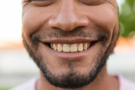 Closeup of smiling male face. Young Latin man with black stubble giving toothy smile. Dental care concept Banque d'images - 129174446